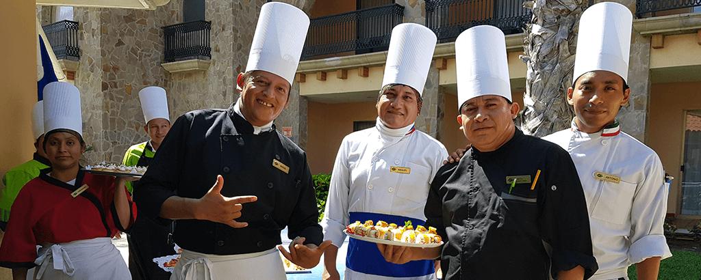 Chefs Repartiendo platillos por la Alberca de Royal Solaris Cabos